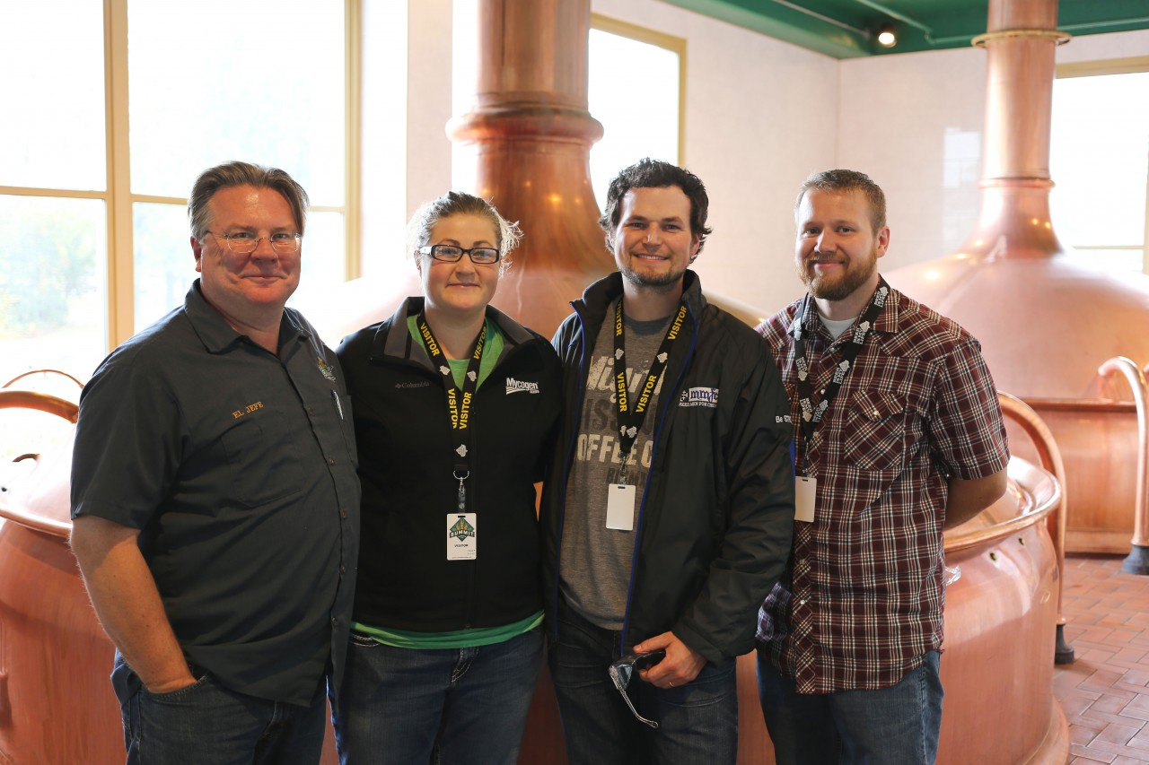 In the brewhouse at Summit Brewing Company. Standing next to his iconic copper brewing tanks is President Mark Stutrud along with Lodge Manager Olivia Stenvold, Phillip Breker and Chef Daniel Miles.